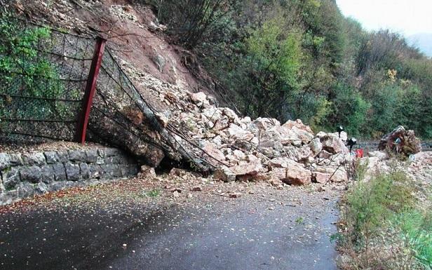 Una frana in roccia che si abbatte su una strada
