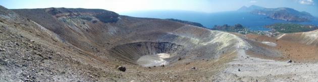 Fig. 1 - Panoramica del Gran Cratere La Fossa ricoperto dai prodotti eruttivi dell'eruzione del 1888-1890. Le zone con una colorazione chiara indicano i punti attuali delle emissioni gassose del vulcano. Sulla destra in secondo piano si nota Vulcanello, l'istmo che separa l'isola da Lipari e i due coni di Salina. (Foto di Guglielmo Manitta)