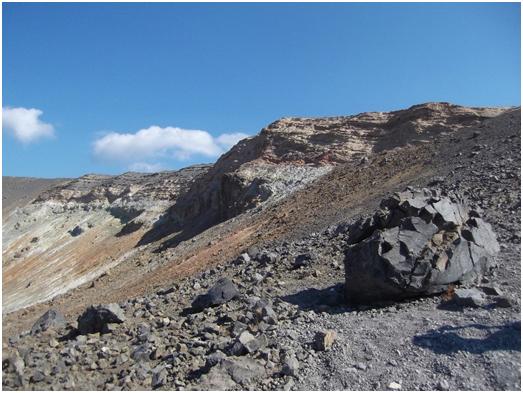 Fig. 5 - Bordo meridionale del cratere La Fossa. In primo piano si nota una grossa bomba espulsa durante la fase eruttiva degli anni 1888-1890 e altri prodotti della stessa eruzione. In fondo, invece, è ben evidente la stratigrafia delle formazioni di Pietre Cotte, più in alto, risalente al 1739 e quella Carruggi. (Foto di Guglielmo Manitta)