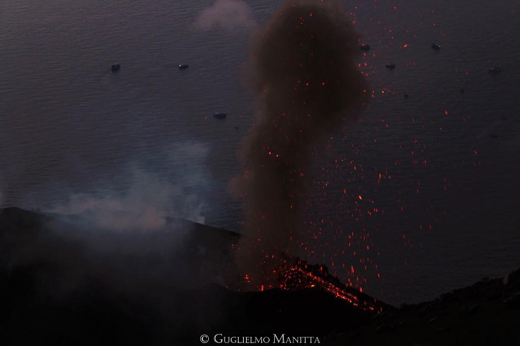 Esplosione ai crateri dello Stromboli caratterizzata dal lancio di materiale incandescente e dall'emissione di cenere. Sullo sfondo le imbarcazioni nel tratto di mare prospiciente alla Sciara del Fuoco. (foto di Guglielmo Manitta)